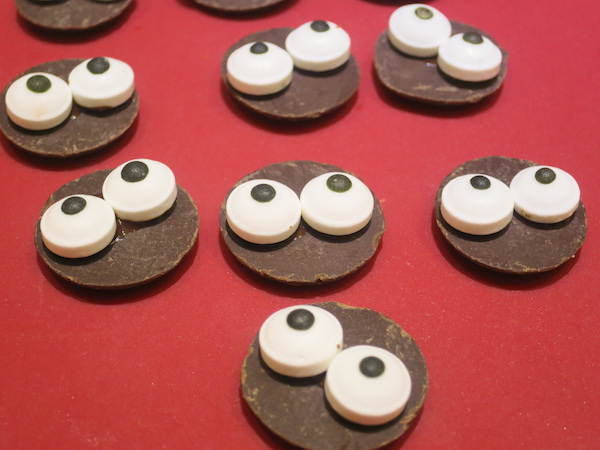 Melt the white chocolate and attach candy eyeballs to flat side of chocolate button with a drop of melted chocolate.